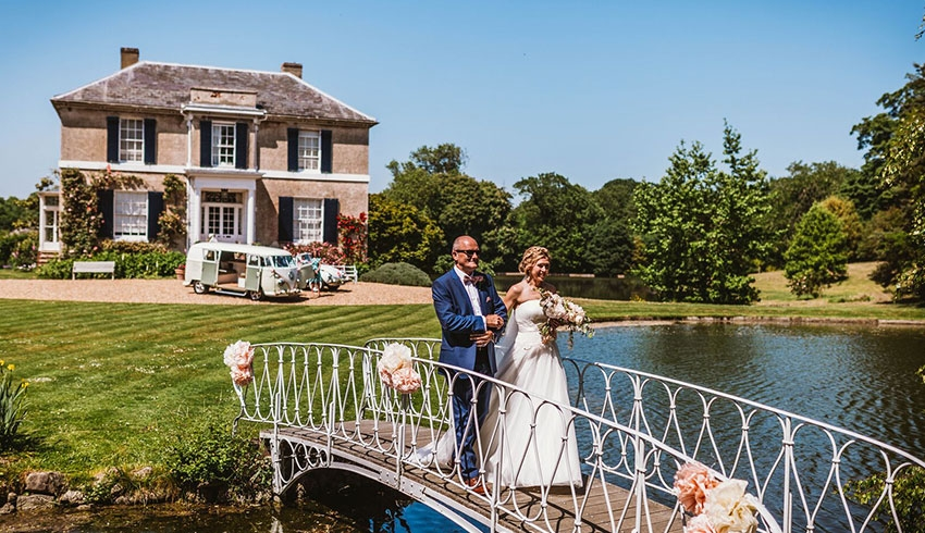 A bride being escorted to her wedding by her Father, both walking across the bridge over to the moated island