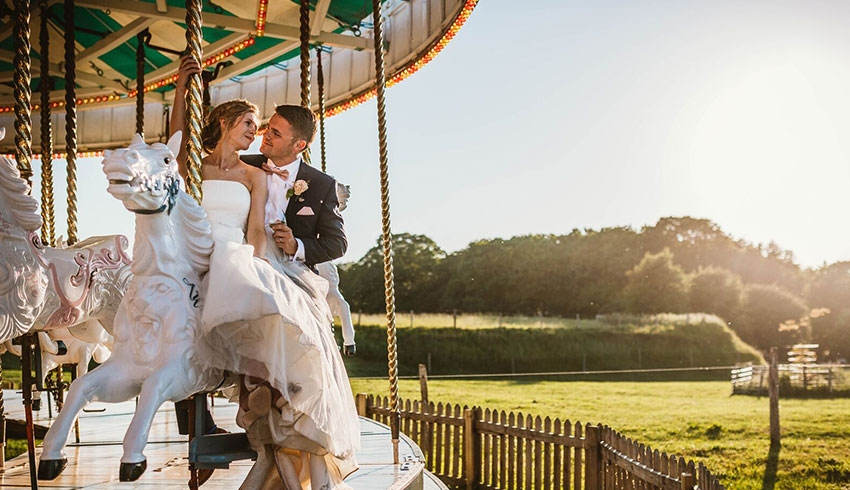 Wedding couple sitting on the carousel and kissing at Preston Court