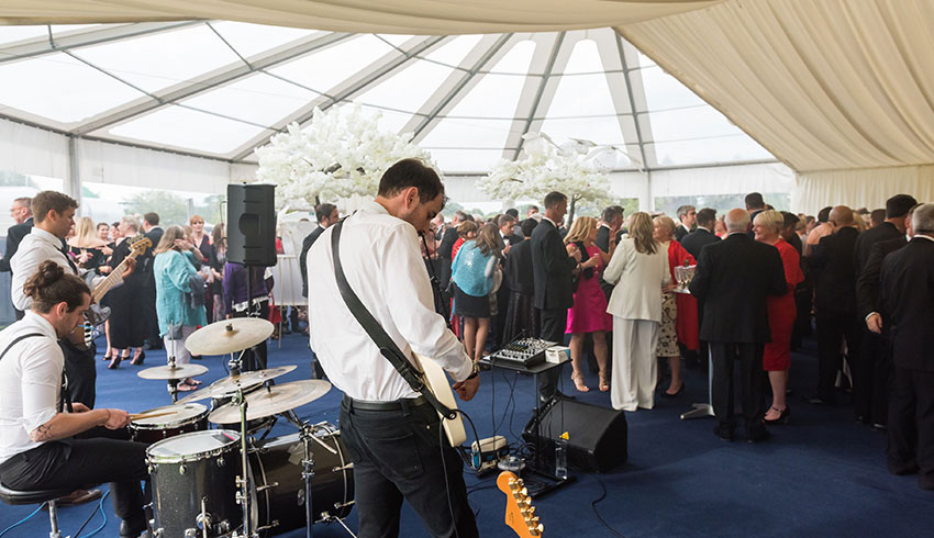 The Alchemists wedding band playing at a marquee wedding