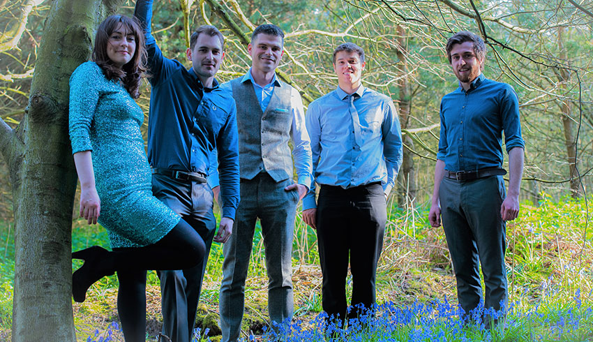 The Alchemists wedding band standing in a bluebell wood