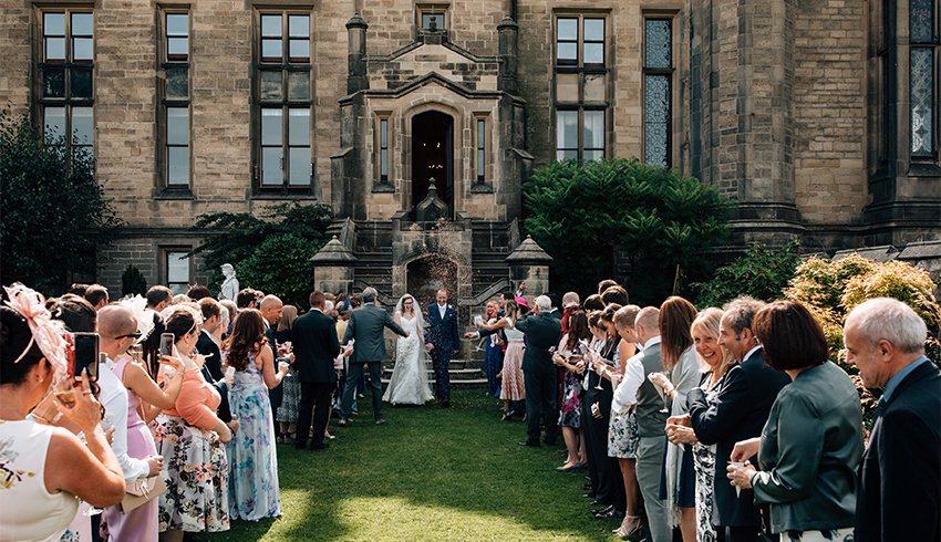 Wedding couple being greeted by their wedding guests after their wedding ceremony at Allerton Castle