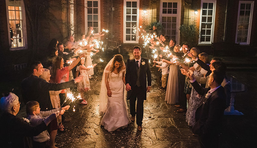 A wedding couple leaving their wedding celebration through a tunnel of sparklers and wedding guests