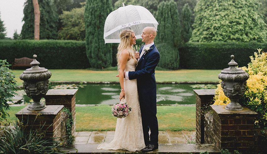 A wedding couple embracing in the rain by the pond at Barnett Hill Hotel