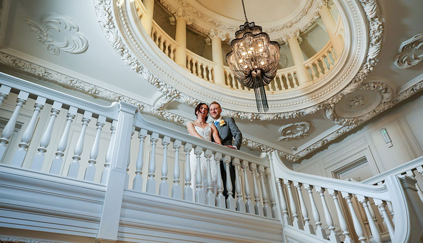A wedding couple standing on the elegant staircase in Barnett Hill Hotel