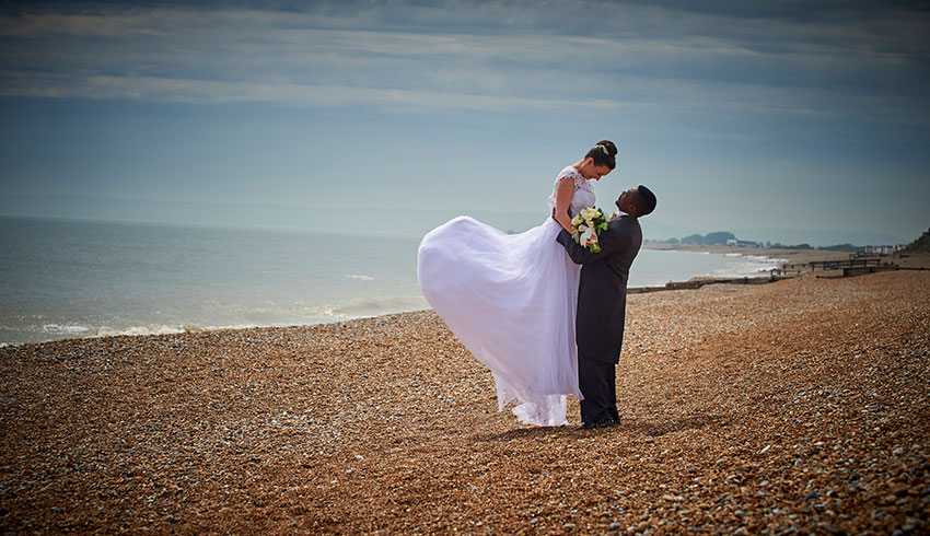 Wedding couple on the beach outside the Cooden Beach Hotel, a wedding venue in East Sussex