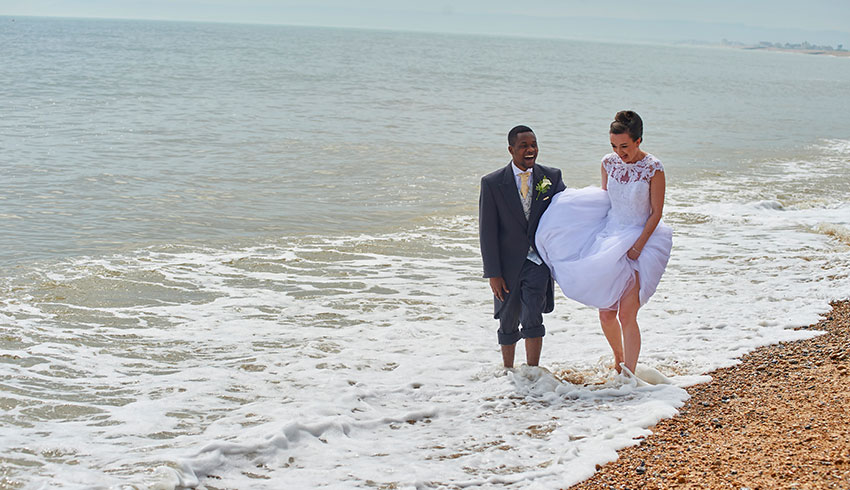 Wedding couple walking in the sea after a wedding at the Cooden Beach Hotel