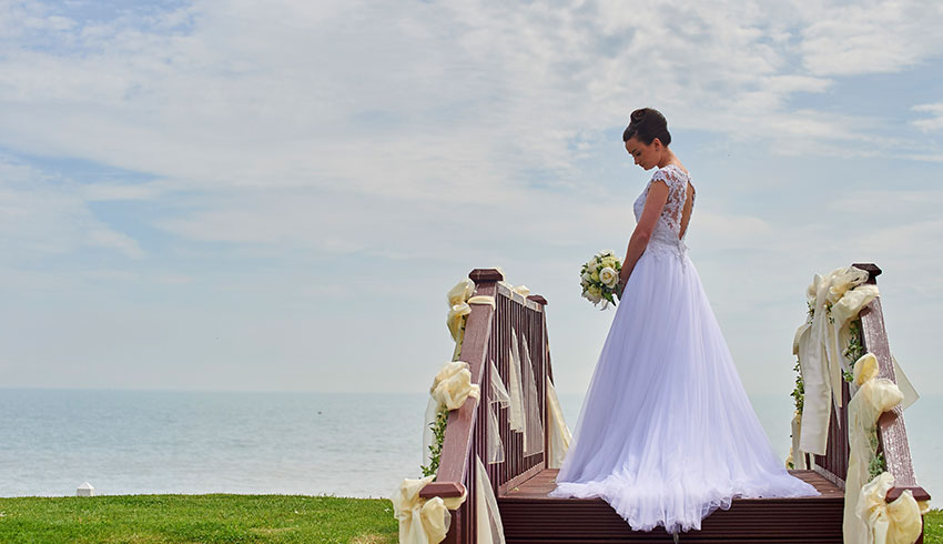 Bride on steps outside the Cooden Beach Hotel