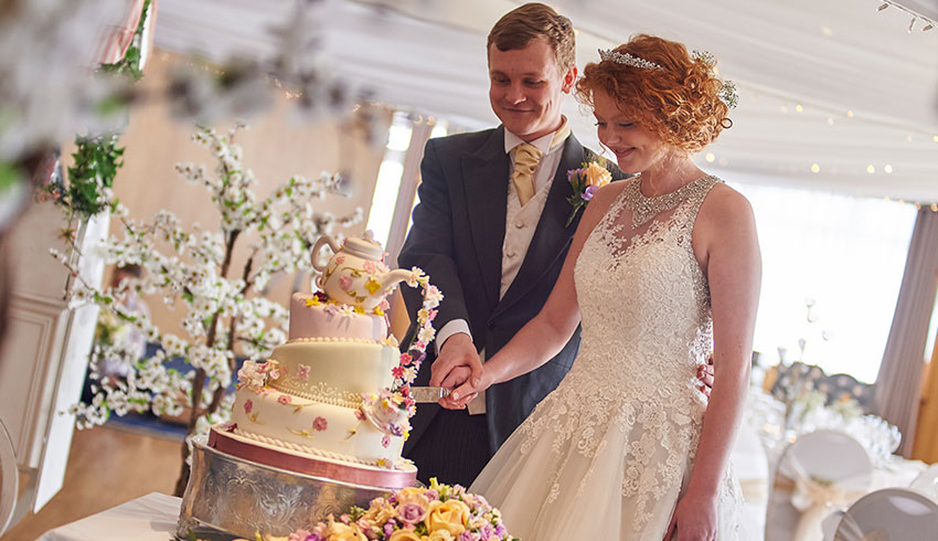 Wedding couple cutting vintage wedding cake at the Cooden Beach Hotel
