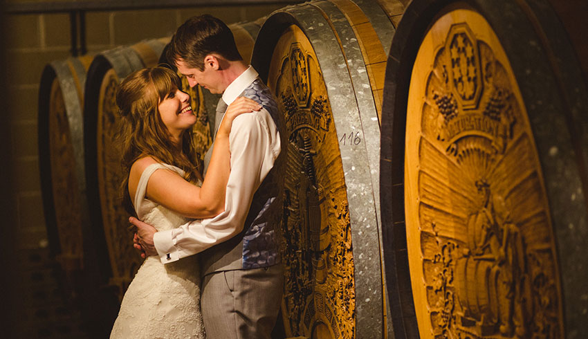 A wedding couple in the wine vaults at Denbies Wine Estate