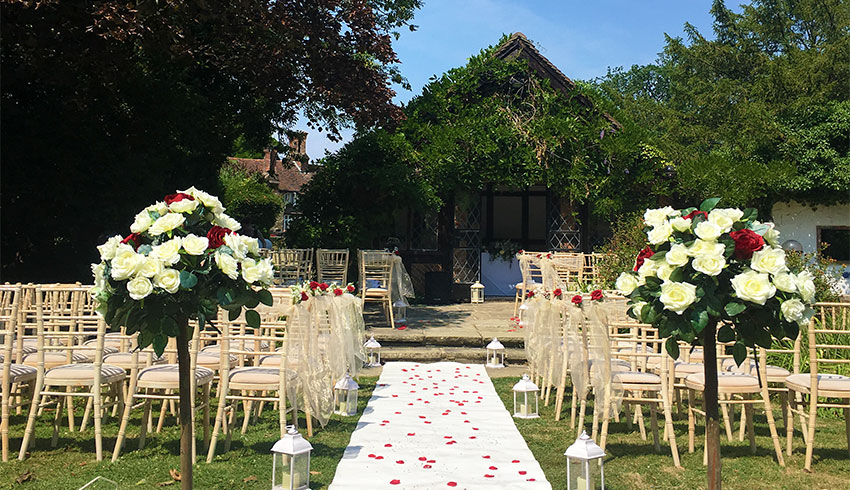The Summer House set up for a wedding ceremony on a beautiful summer day, with wedding flowers and petals
