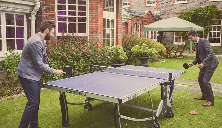 Wedding guests playing table tennis at a wedding in the grounds of Gildredge Manor
