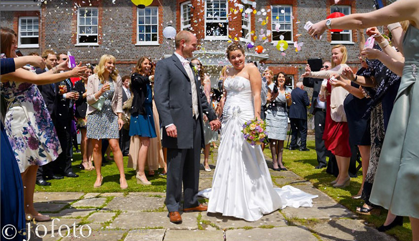 Wedding couple at Gildredge Manor outside with their wedding guests, who are throwing confetti over the newly married couple