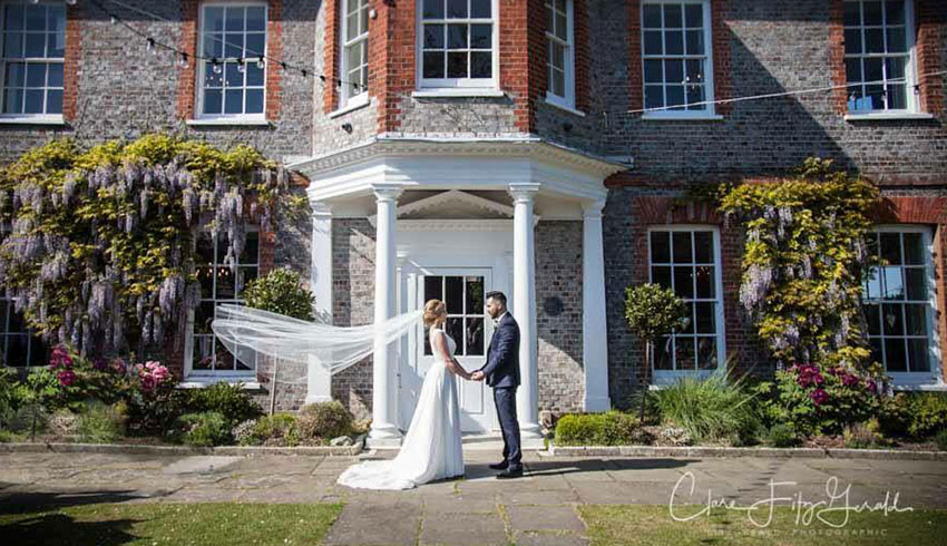 Wedding couple outside the main entrance to Gildredge Manor