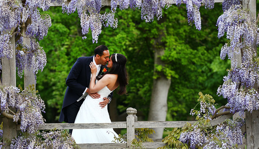 Bride and Groom in the formal gardens at Great Fosters, a Surrey wedding venue