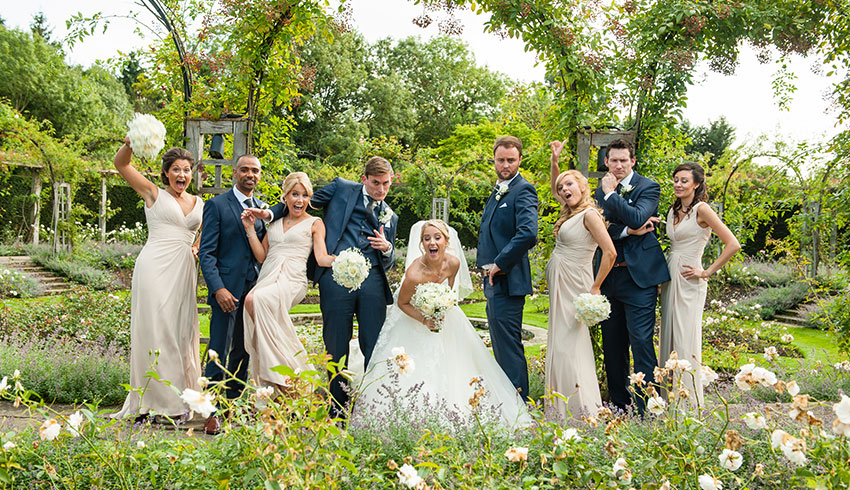 Bridal party in the rose garden at Great Fosters, a Surrey wedding venue