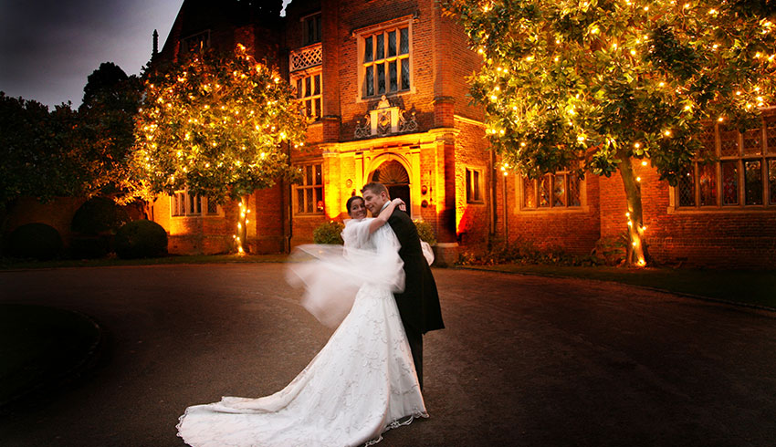 Bride and Groom outside the front of Great Fosters at night
