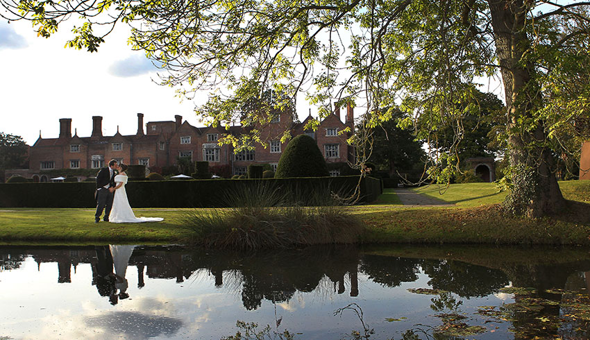 Bride and Groom by the moat at Great Fosters, a Surrey wedding venue