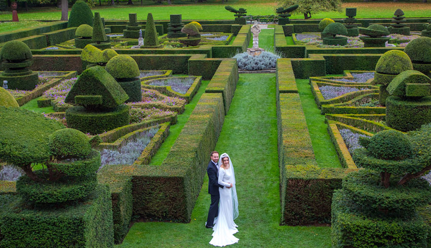 Bride and Groom by the topiary at Great Fosters