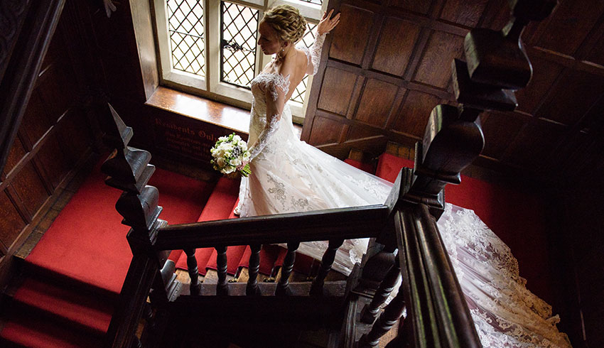 Bride coming down the sweeping staircase at Great Fosters, a Surrey wedding venue