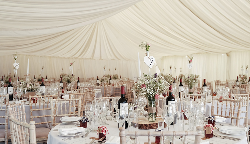 A wedding marquee with pretty table arrangements at the Highden Estate