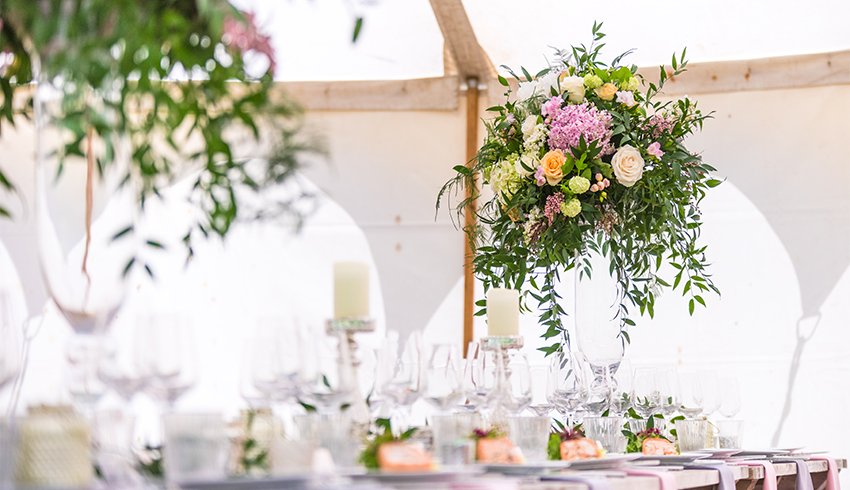 Colourful flower arrangements for a wedding in a marquee at the Highden Estate