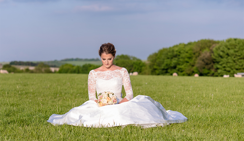 A bride sitting in one of the fields at the heighten Estate