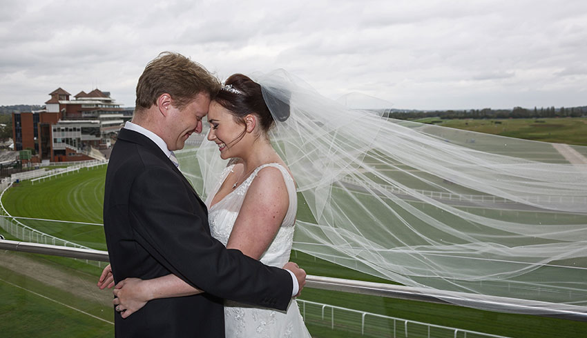 A bride and Groom embracing at the Racecourse at Newbury