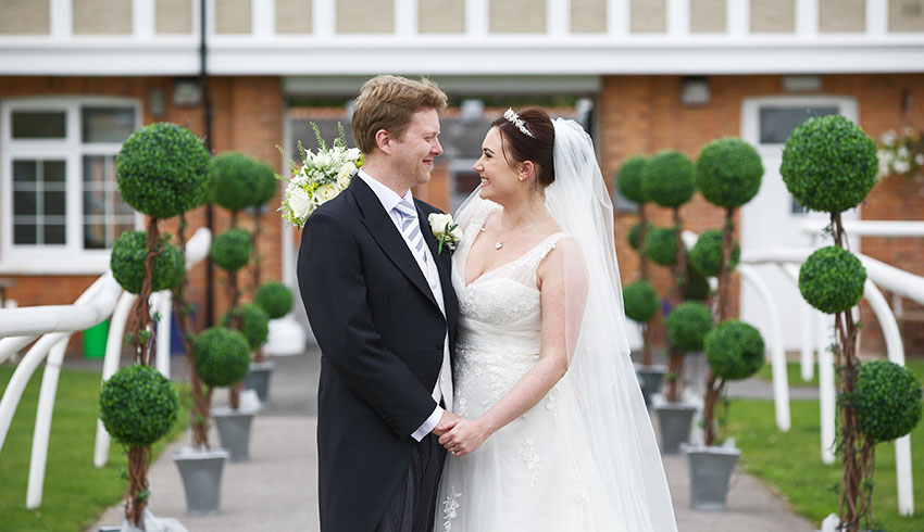 A wedding couple outside the Stables at Newbury Racecourse wedding venue in Berkshire