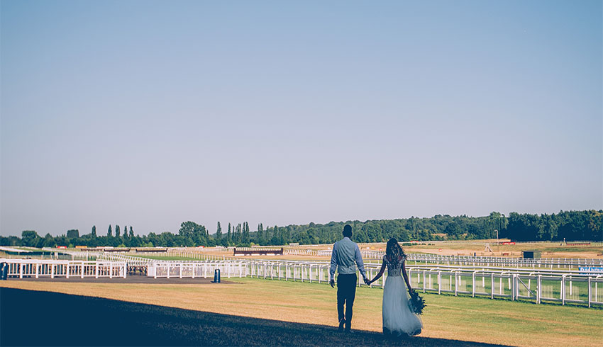 Wedding couple walking hand in hand across Newbury Racecourse on their wedding day