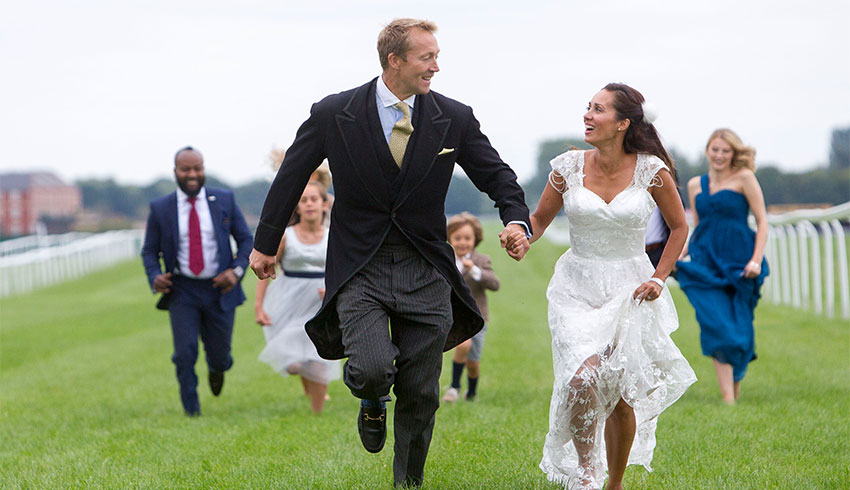 Wedding party running along the racecourse at Newbury Racecourse wedding venue