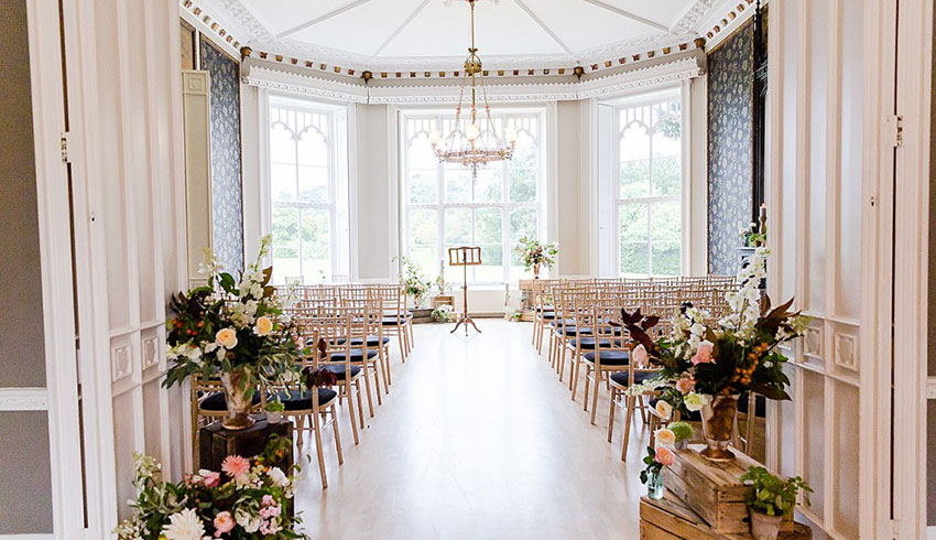 Pink theming of the beautiful wedding ceremony room at Nonsuch Mansion, a Surrey wedding venue