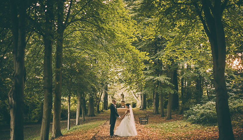 Wedding couple walking through the grounds of Port Lympne Hotel