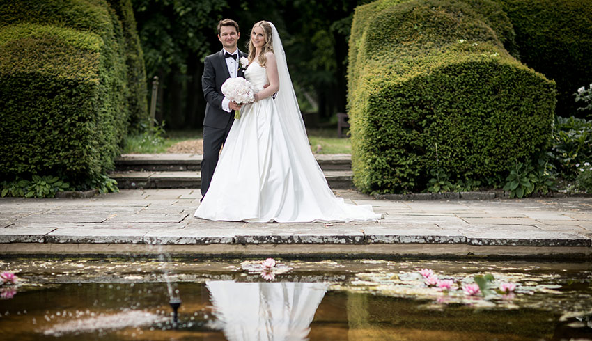 Wedding couple by the pond in the gardens at Port Lympne Hotel