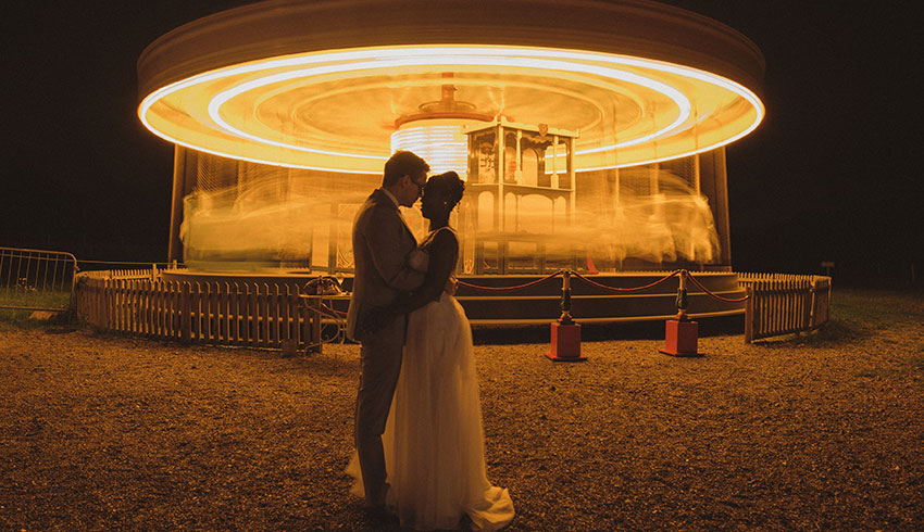 A bride and groom kissing in front of the Victorian carousel at the end of their wedding evening