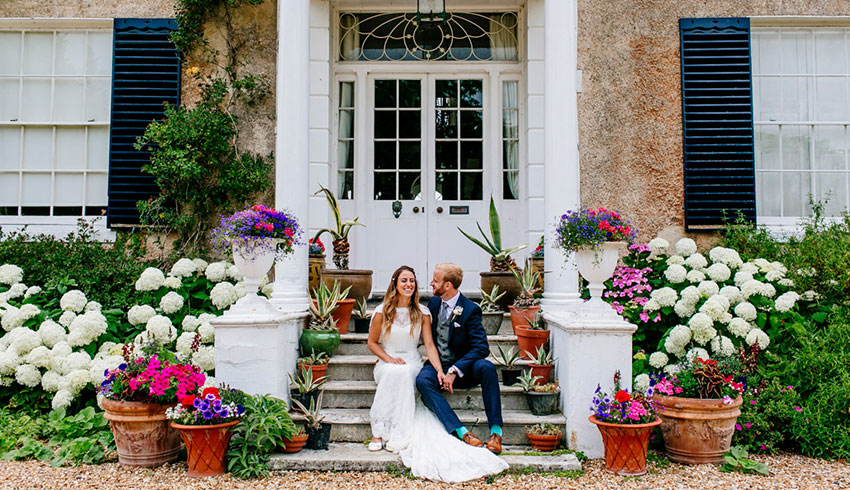A bride and Groom sitting on the steps of the country house at Preston Court surrounded by pretty, colourful flowers
