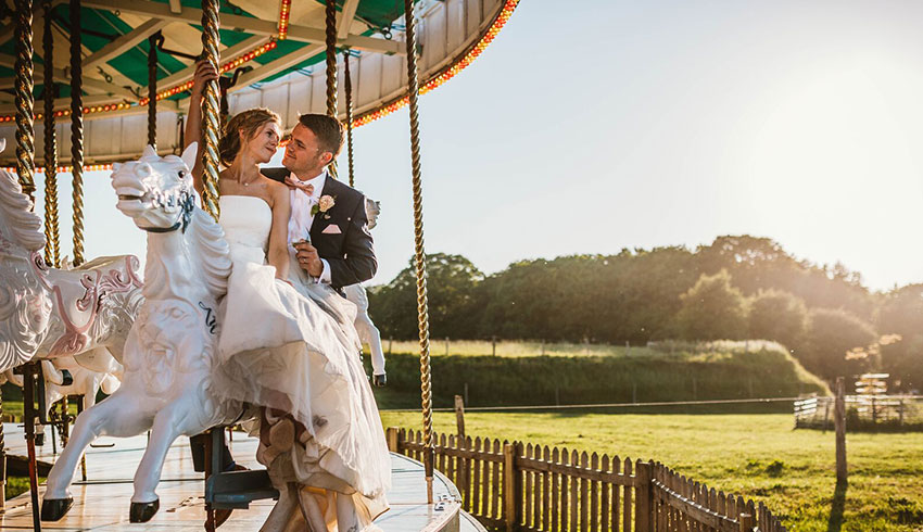 A bride and groom on the Victorian carousel at Preston Court