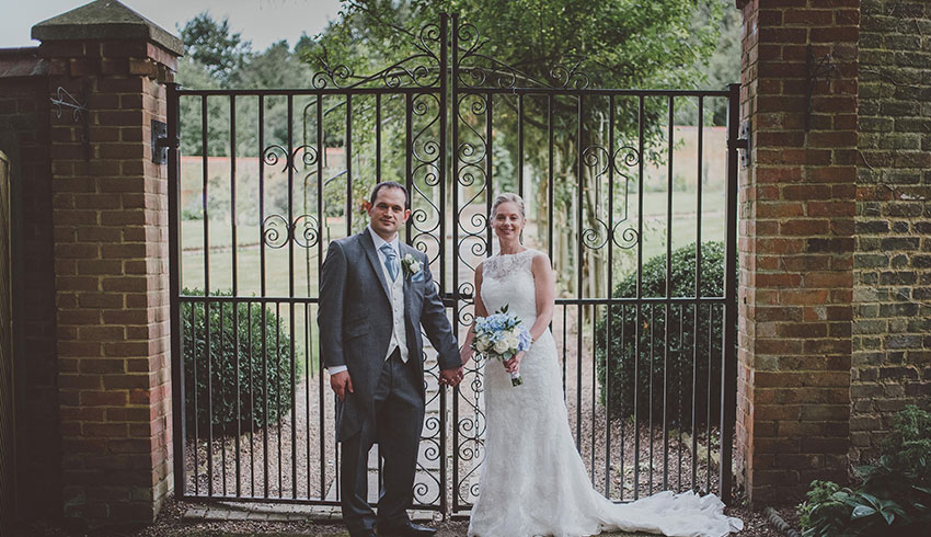 The grounds and iron gates behind a wedding couple at Rowhill Grange