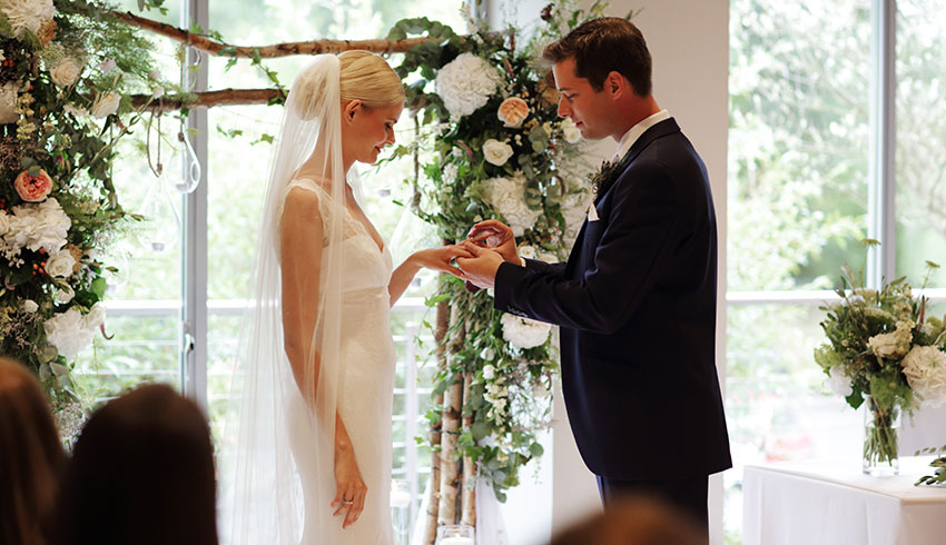 Bride and Groom exchanging their vows at a wedding at the Runnymede Hotel