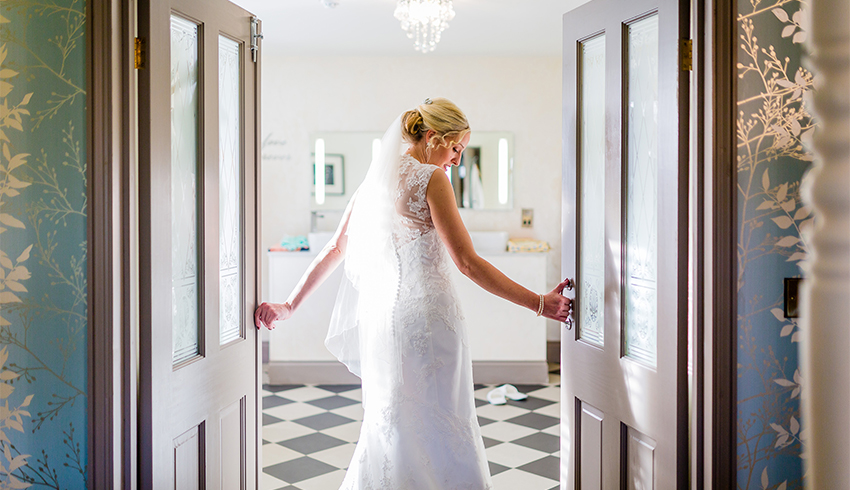 A bride walking through the doors of Southdowns Manor
