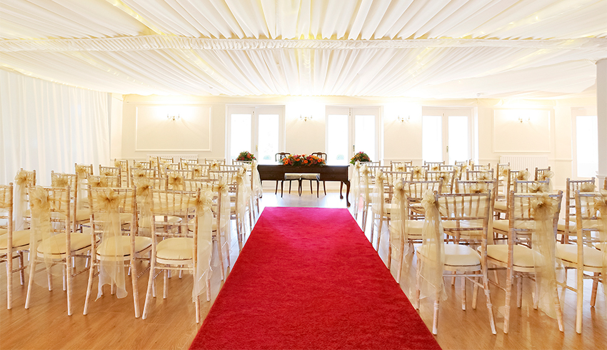 Red and cream wedding ceremony theme at Southdowns Manor