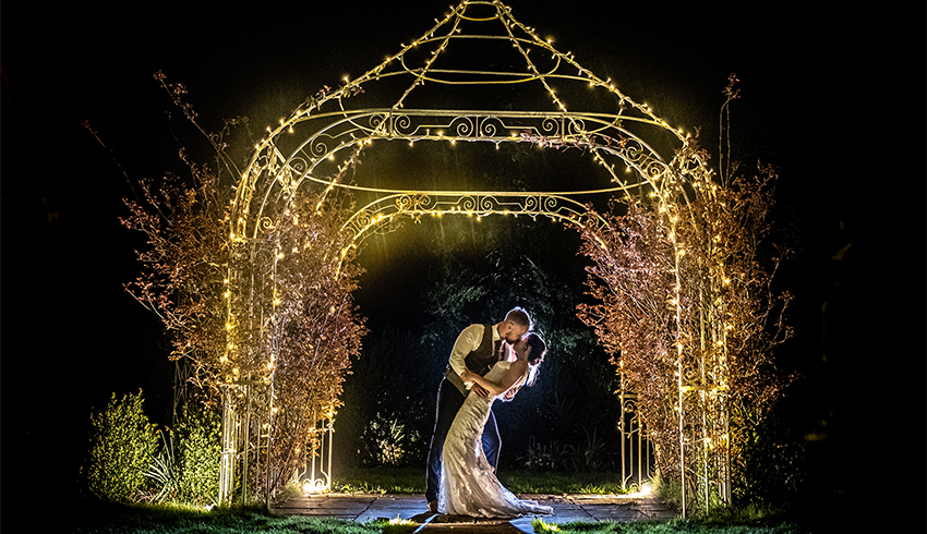 Wedding couple embracing under a lit-up pergola at night in the gardens of Southdowns Manor