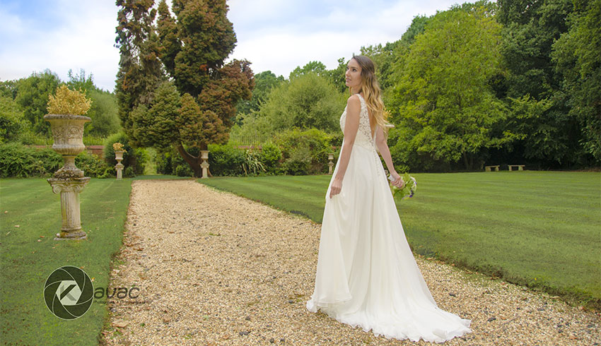 A bride walking in the grounds of Stanhill Court, a Surrey wedding venue