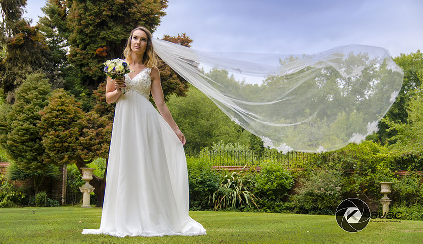 A bride with her veil blowing in the wind at Stanhill Court
