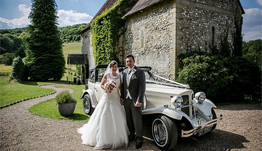 A wedding couple, just married and standing outside The Lost Village of Dode, a wedding venue in Kent