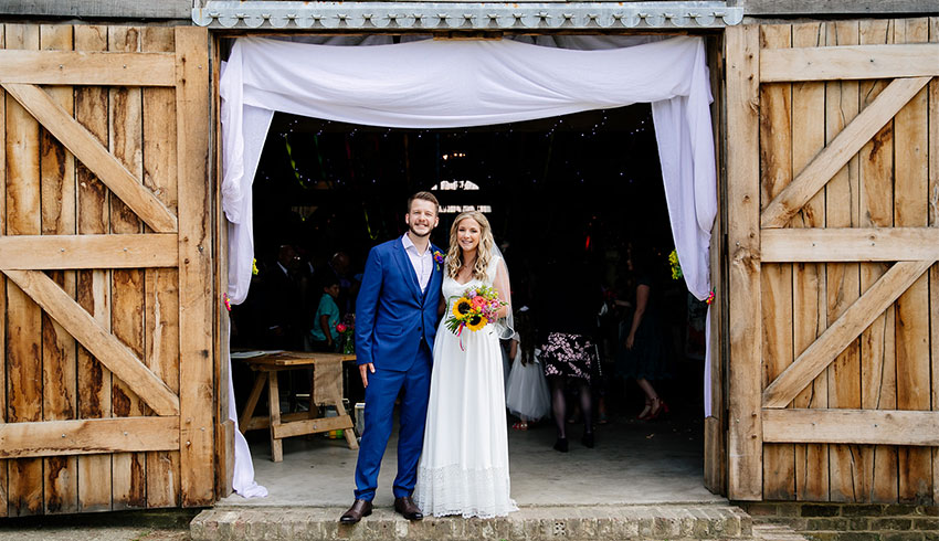 Wedding couple at the entrance of the barn at the Yoghurt Rooms, East Grinstead wedding venue