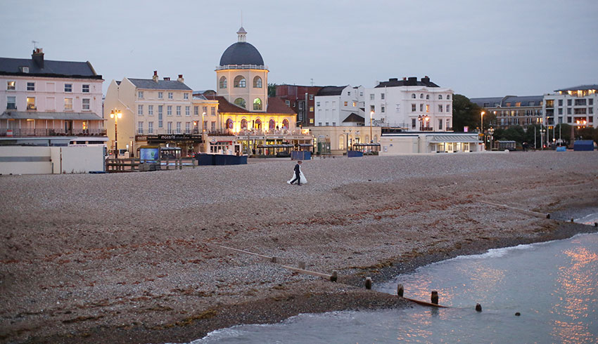 Wedding couple walking along the beach in front of the Worthing Dome, a West Sussex Wedding Venue