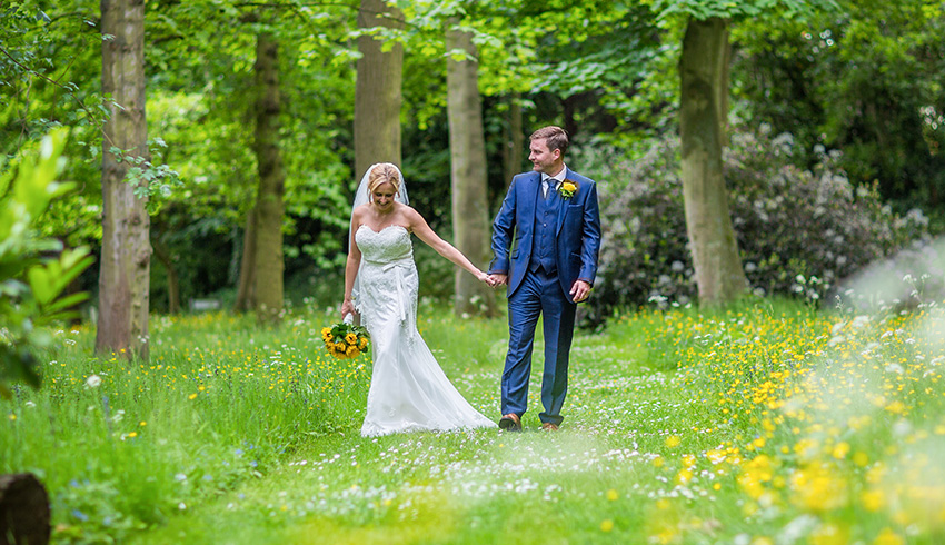 Wedding couple walking through the grounds of Rowhill Grange & Utopia Spa, Kent wedding venue